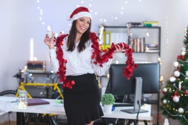 Woman surrounded with Christmas decorations in front of the computer