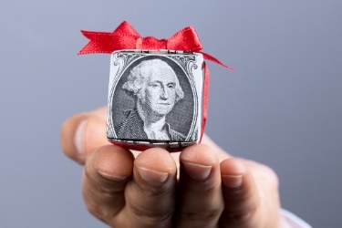 Hand offering a small gift wrapped with a dollar bill