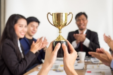Someone at the table holding a trophy while others applaud during a meeting