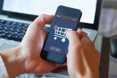 Hands holding a mobile phone with a purchase screen