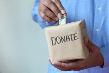 Hands putting money inside a Donation Box
