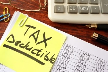 """Stack of files with a post it that says """"Tax Deductible"""""""