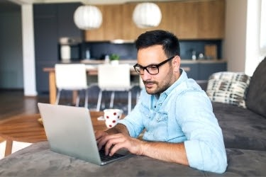 Man working on his laptop remotely from his home