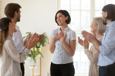 People at work applauding a woman standing in the middle