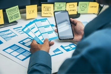 Man working on user experience website layout on mobile version