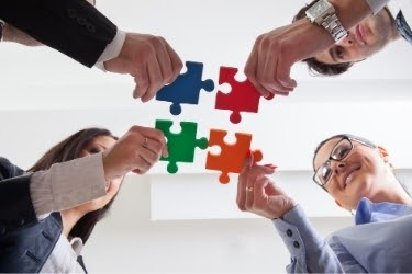 Company workers connecting a few puzzle pieces together