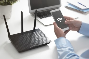 Man using Wifi on his mobile phone next to the router