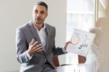Man talking about the opportunities while holding sales graphics