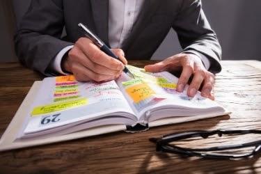 Man writing in an agenda