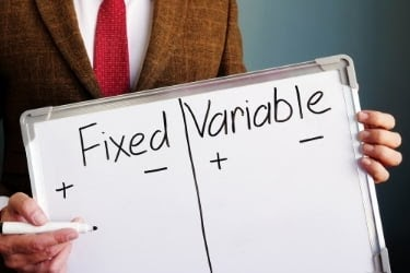 Man holding a whiteboard with the word Fixed and Variable