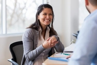 Woman dressed in a business attire smiling