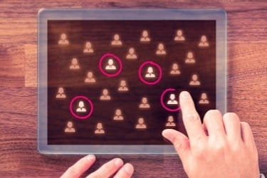 Hand selecting an audience from a pool of people on a tablet