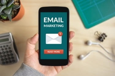 """Hand holding a phone with an image that says """"Email Marketing"""""""