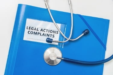 Legal Actions and Complaints in a blue folder with a stethoscope