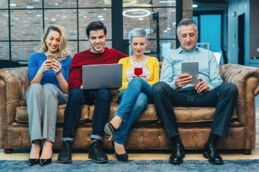 4 people sitting and on their devices