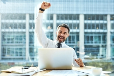 Man celebrating a closed deal in front of his laptop