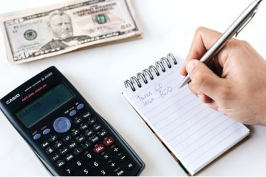 Someone budgeting with a calculator and a notepad