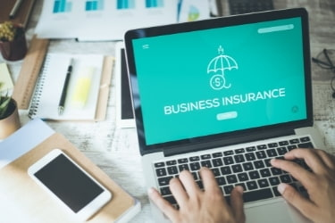 Small business owner looking for Business Insurance in the laptop