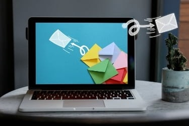 Email Blast Concept - Email letters flying out from the laptop