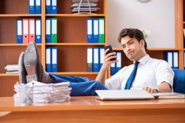 Man checking his mobile phone during working hours