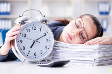 Tired woman with a big clock