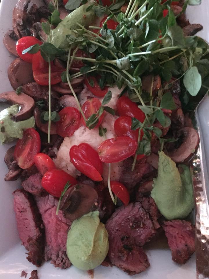 smoked bistro steak with creamed horseradish parmesan potatoes, pea pesto, pea shoots, tomatoes, and a mushroom vinaigrette
