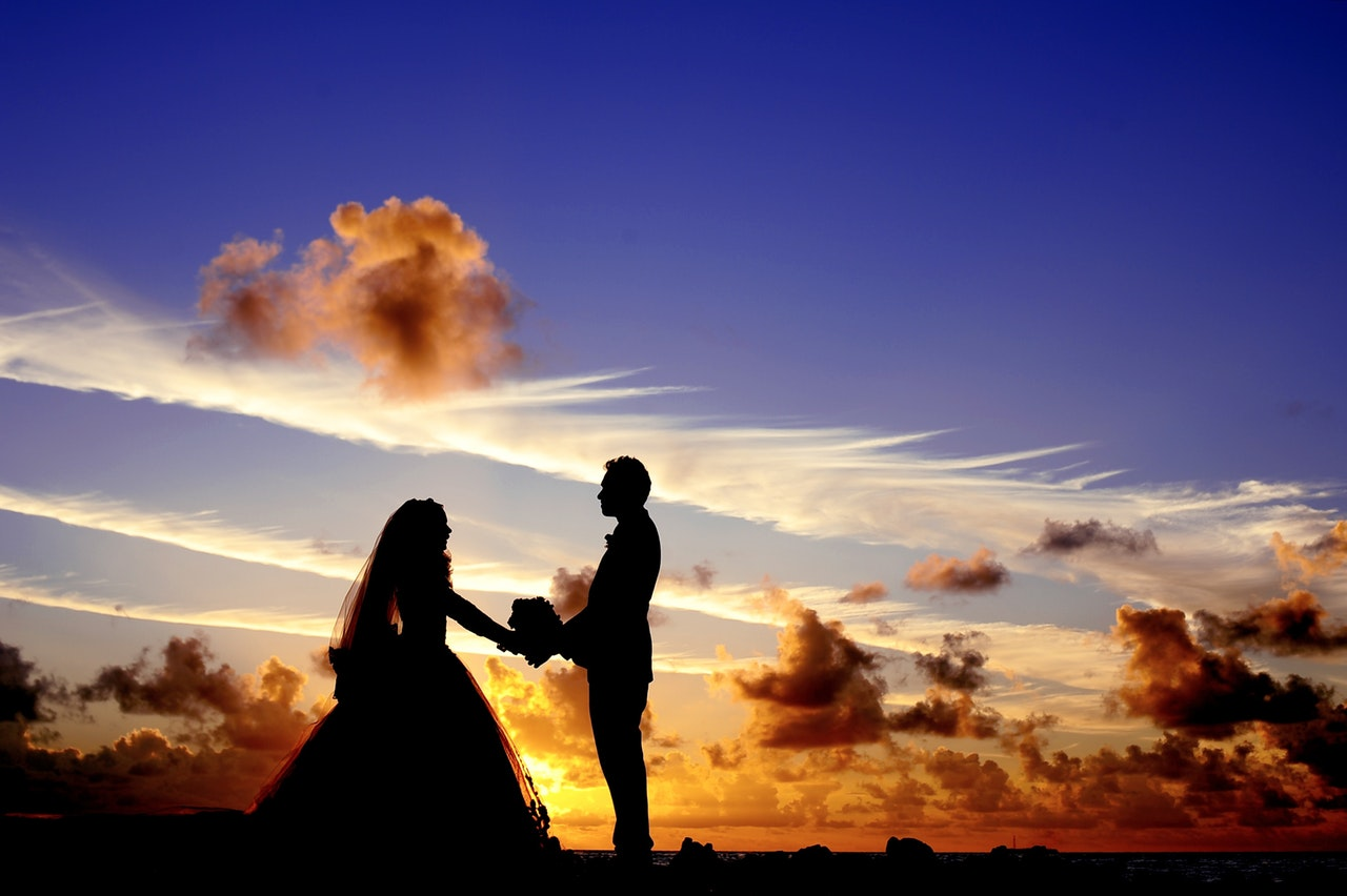 a bride and groom stand silhouetted against a dramatic blue and orange sunset over the ocean