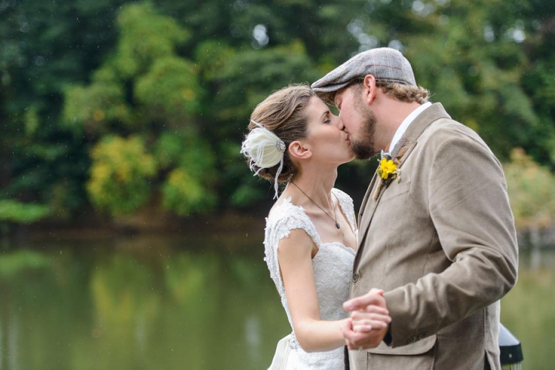 a bride and groom kiss in front of a green pond at wye island nrma