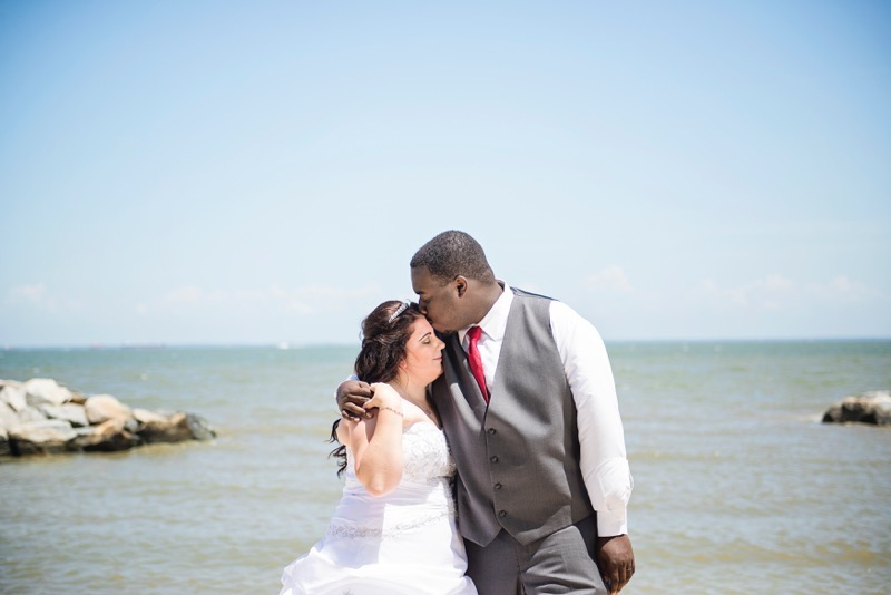 A groom leans over to kiss his bride in front of the sea at mayo beach park in marlyand
