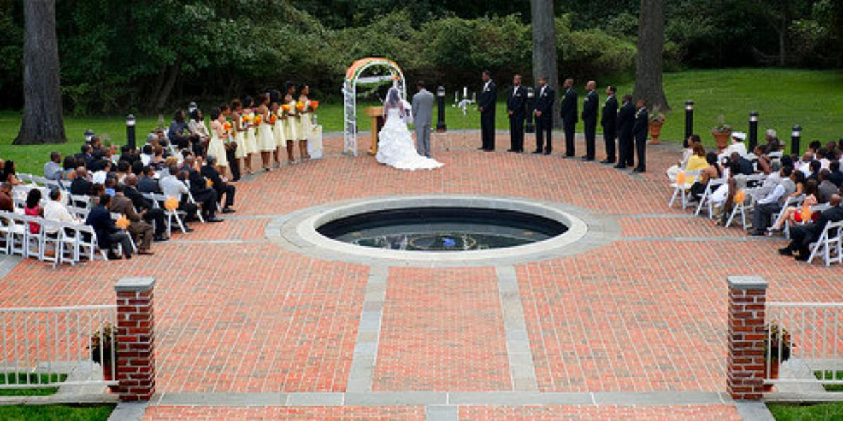 a bride and groom during their wedding ceremony. their friends are arranged in a circle around a fountain behind the happy couple on a red brick patio