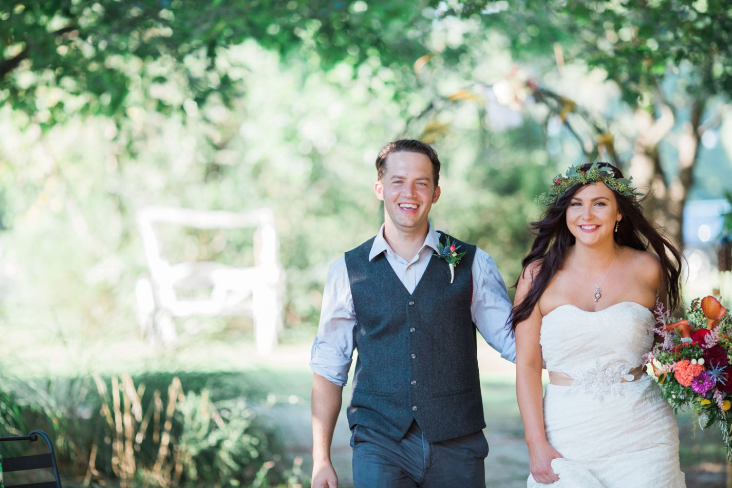 a bride wearing a wreath of flowers on her head and carrying her bouquet walks with her new husband, who has taken his jacket off and rolled up his sleeves