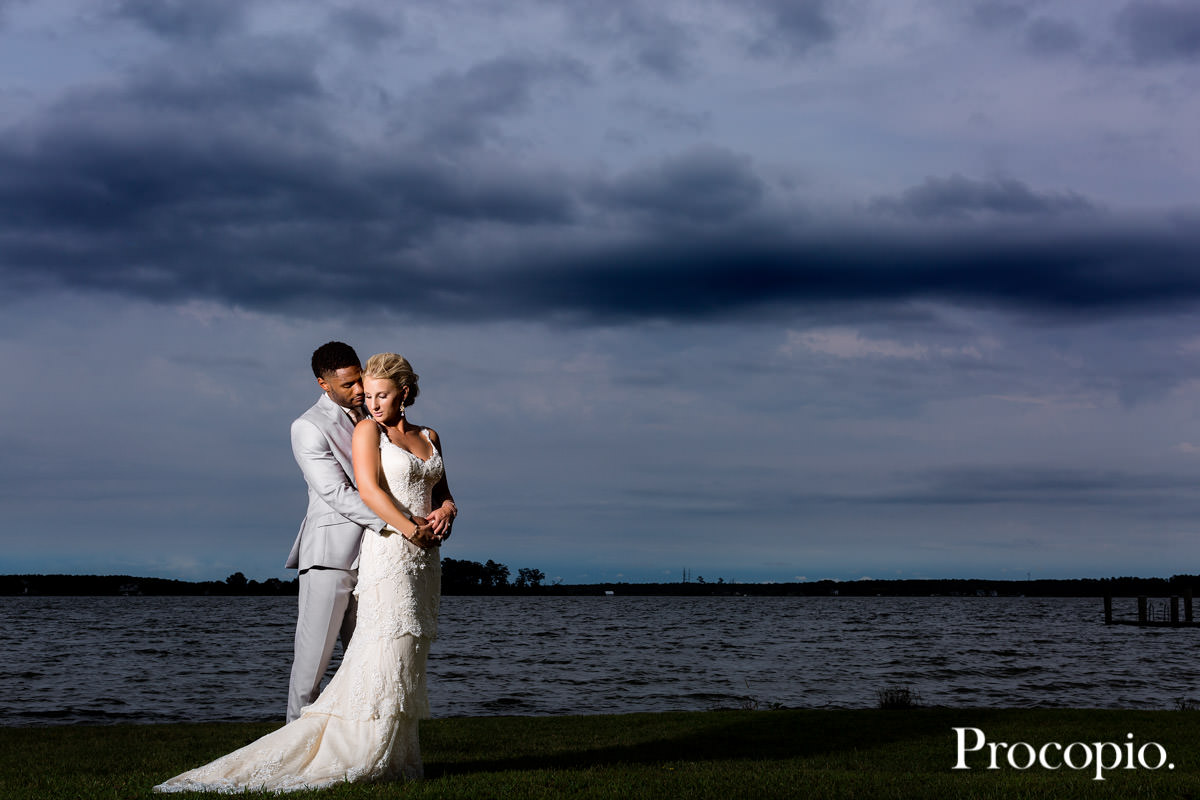 groom and bride posing in front of lake