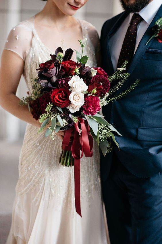 bride holding bouquet of red and white flowers