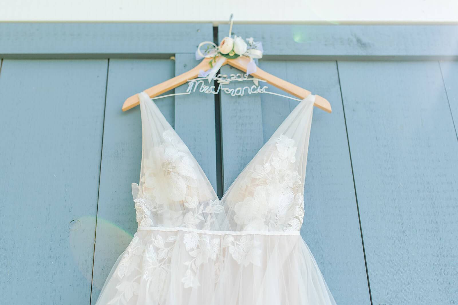 wedding dress hanging on blue barn