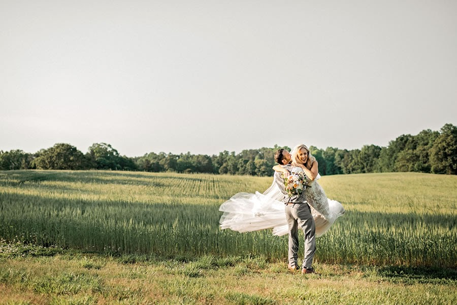 married couple in a field of grass