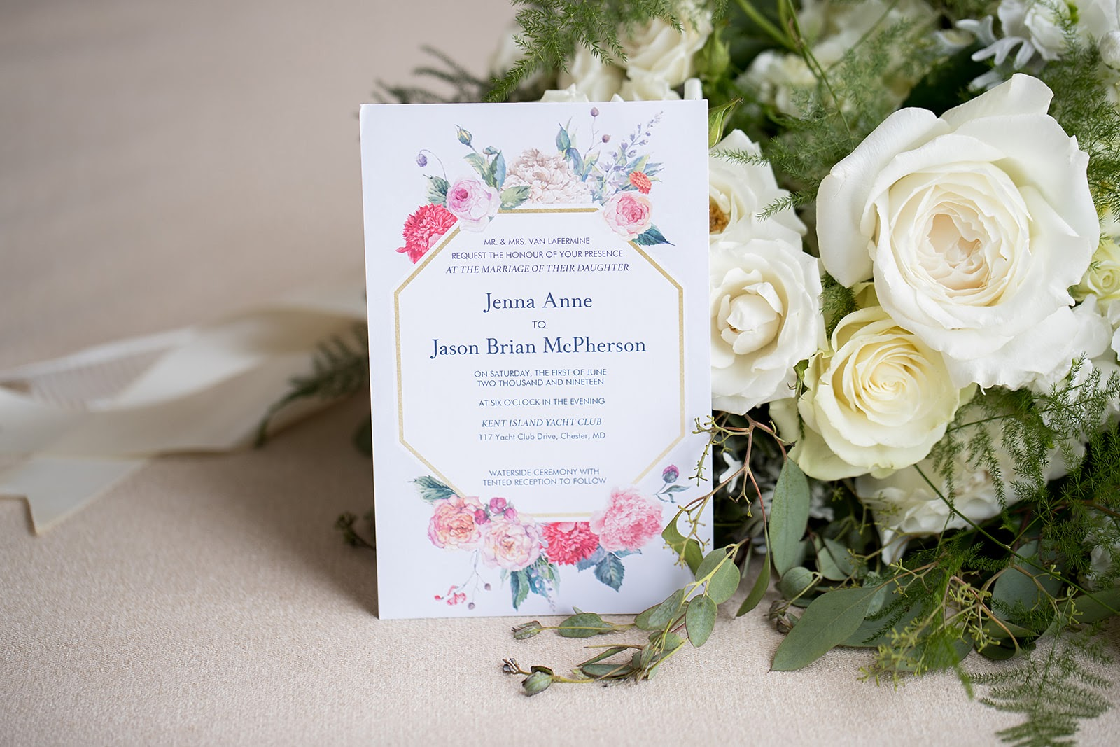 floral wedding invitation beside a bouquet of white roses