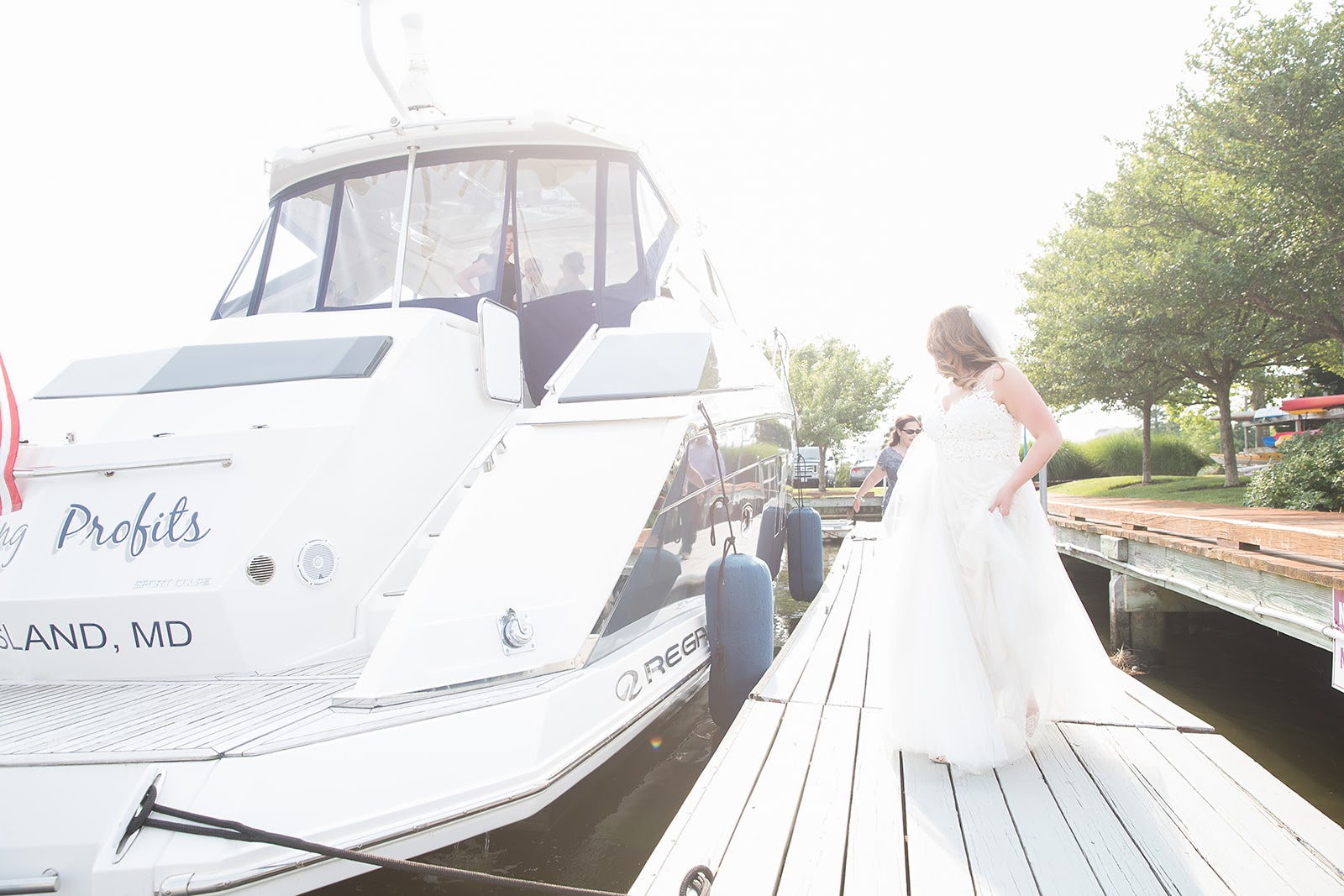 bride in wedding gown walking toward boat
