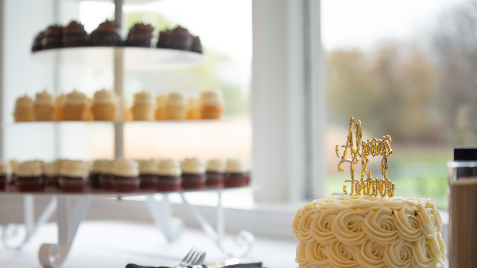closeup of small wedding cake with many in the background