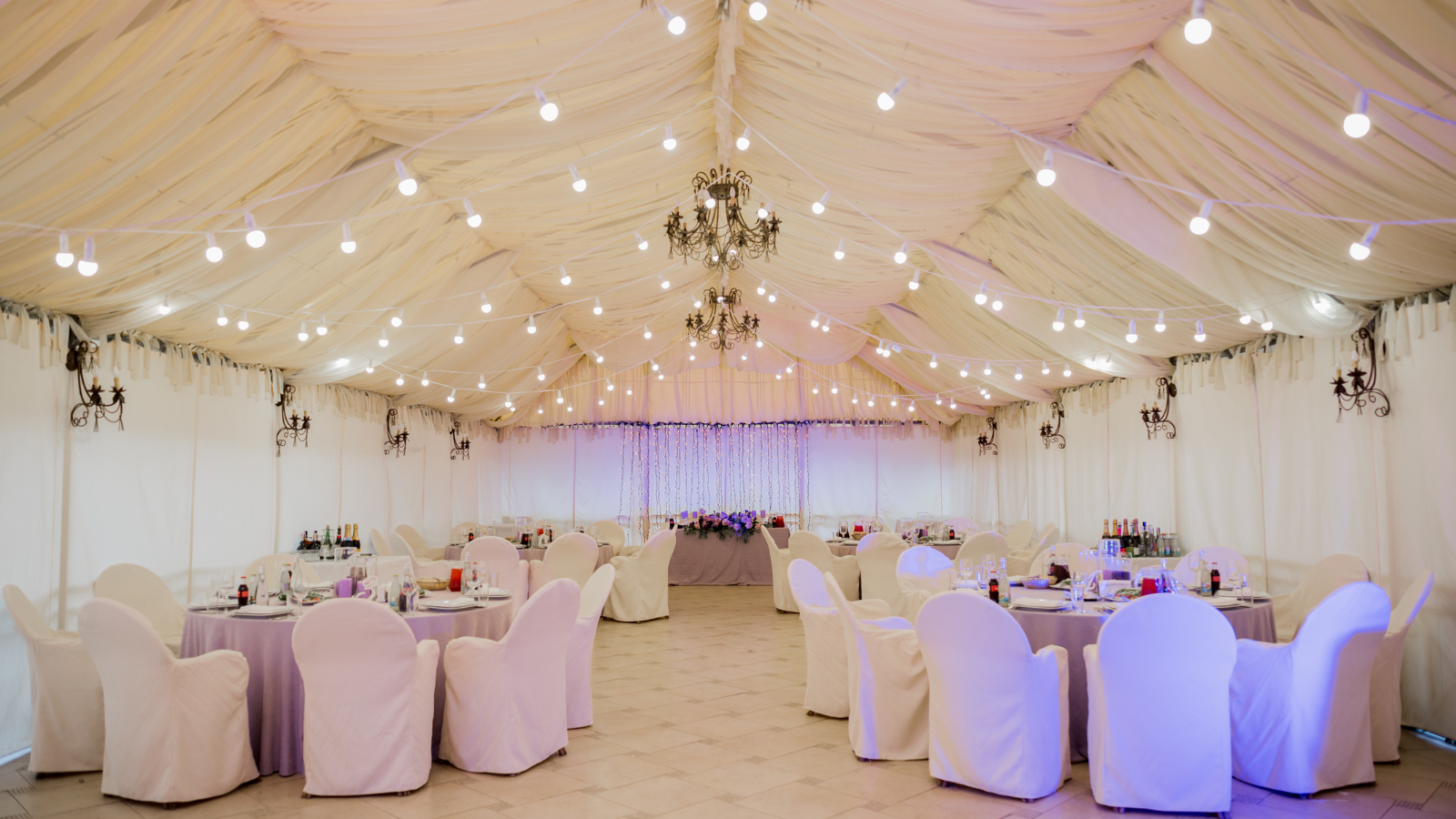 string lights and assorted seating in tent for reception