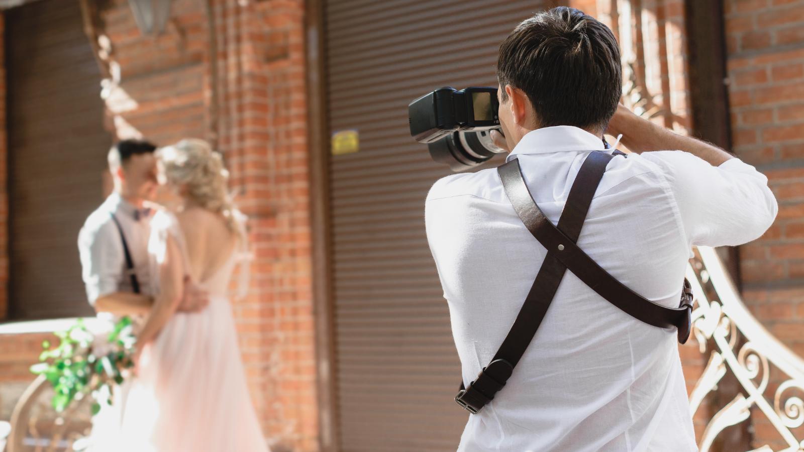 closeup of photographer taking wedding photos of bride and groom