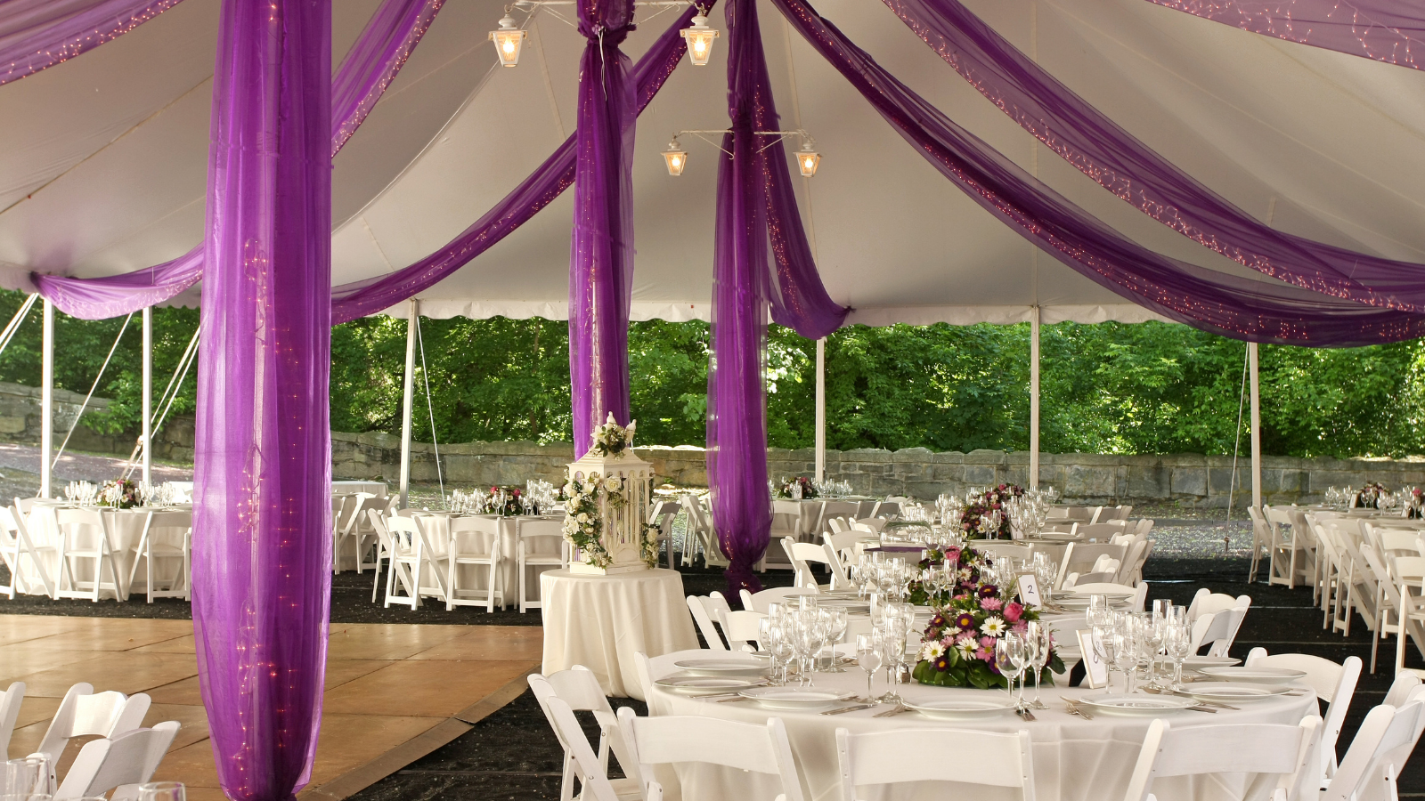 outdoor wedding with purple fabric and string lights draped across the tent