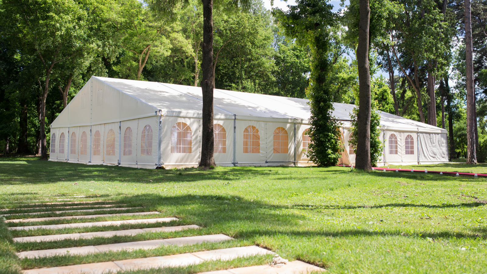 distanced shot of a wedding tent with walls to protect guests from rain