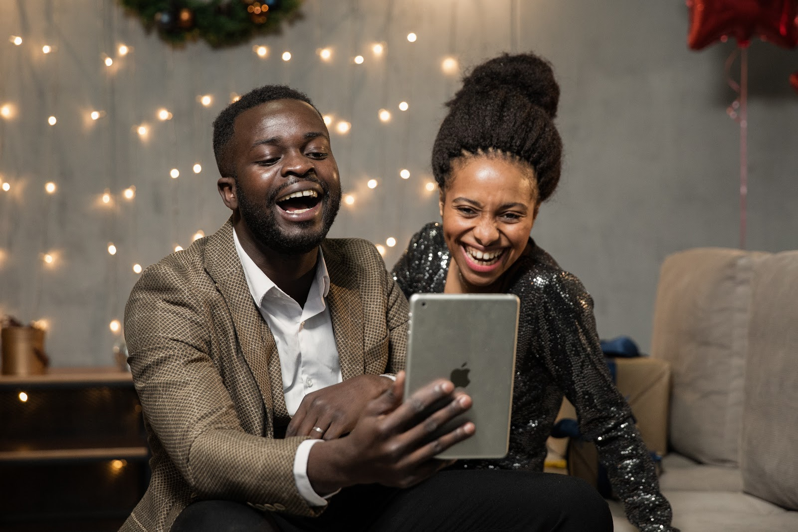 man and woman laughing while holding iPad