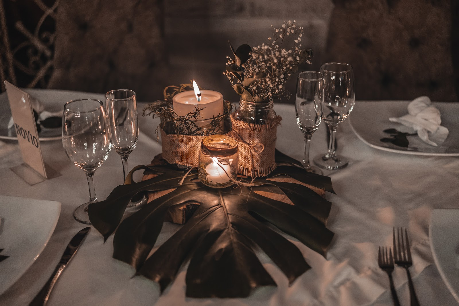 candles on top of a palm leaf as a centerpiece on a table. Wine glasses, plates, and silverware surround the centerpiece