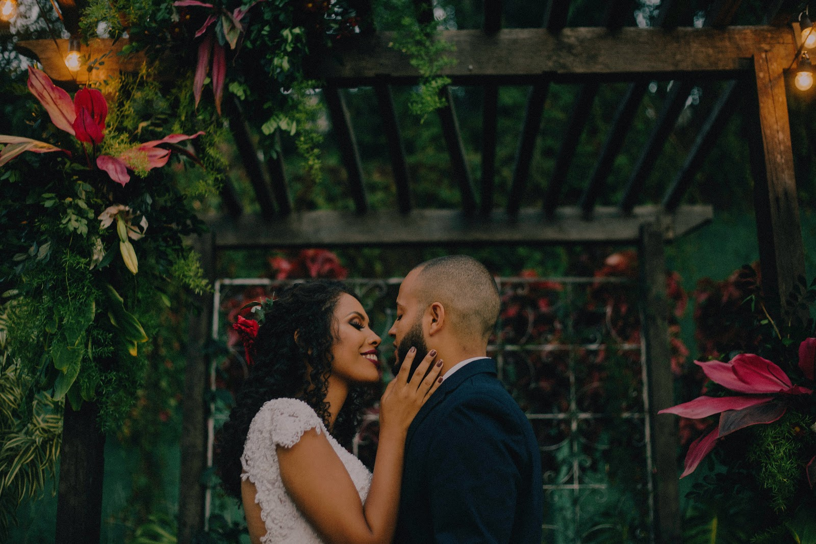 couple holding each other surrounded by greenery
