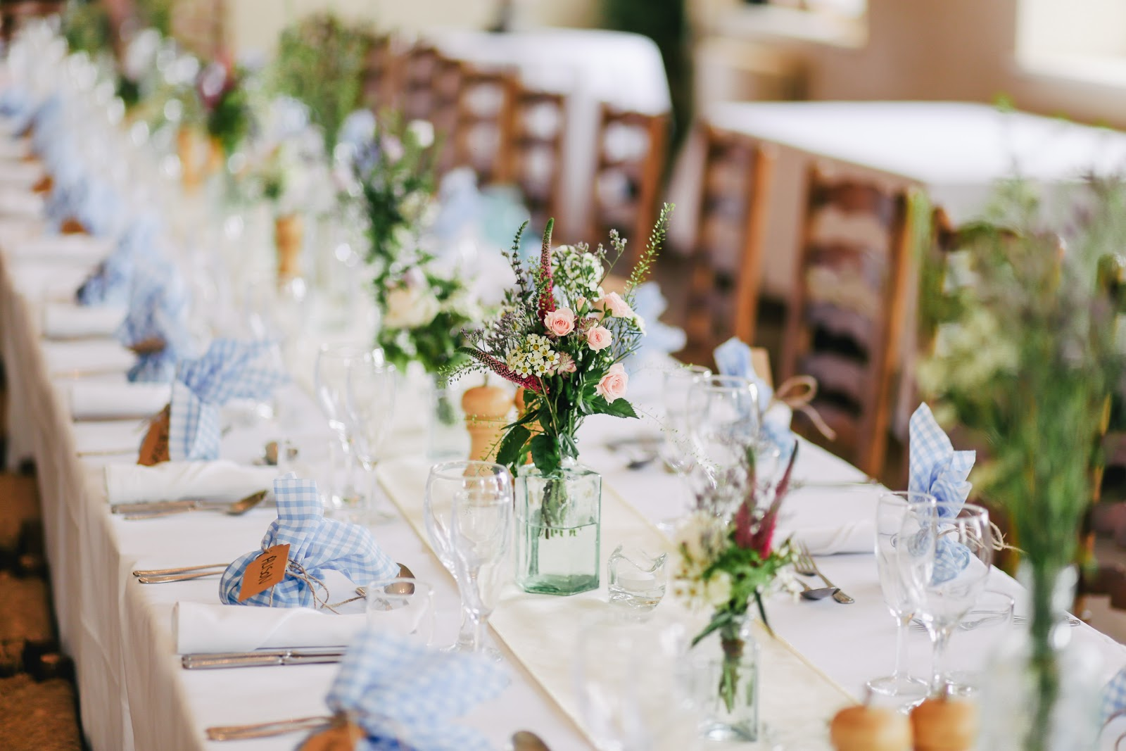 long table with glasses, silverware, and flower centerpieces