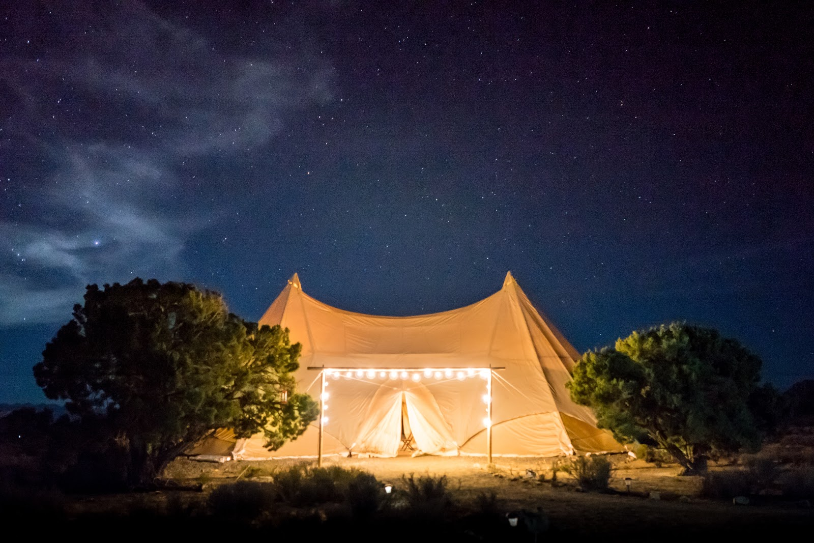 tent lit up by string lights at night time