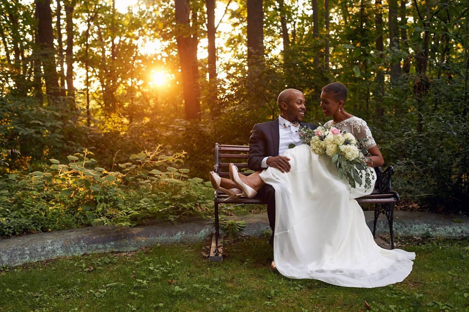 bride and groom sitting on a bench outside
