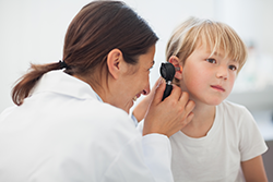 Audiologist examining child's ear with an otoscope