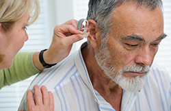 Audiologist fitting a Behind the Ear hearing aid for a hearing loss patient.